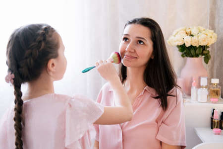 Cute portrait of young mom and daughter making make up for her