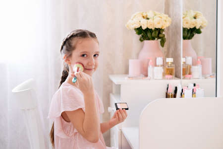 Cute little young lady doing make up in a bedroom. Light and airy portrait.