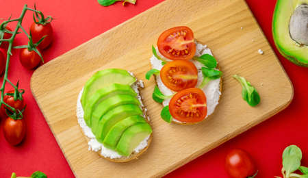 Top view flat lay toast with cottage cheese, avocado and sliced cherry tomatoes wooden board red background, healthy food concept
