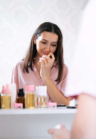 Beautiful caucasian woman smell perfume in a bedroom, reflection in a mirror portrait.