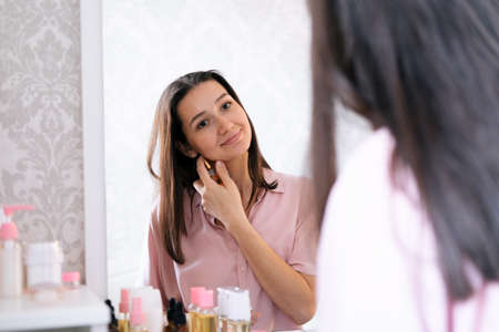 Beautiful caucasian woman use perfume in a bedroom, reflection in a mirror portrait.
