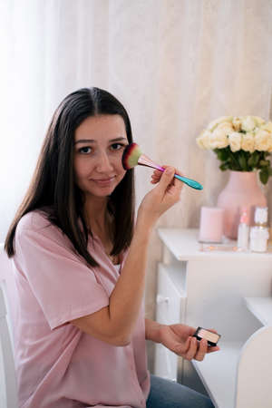 Cute young woman doing make up at home