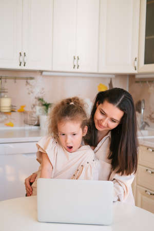 Cute portrait of mother and daughter sitting in a kitchen table and using computer. Banco de Imagens