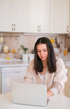Young beautiful caucasian woman using laptop, sitting in kitchen.