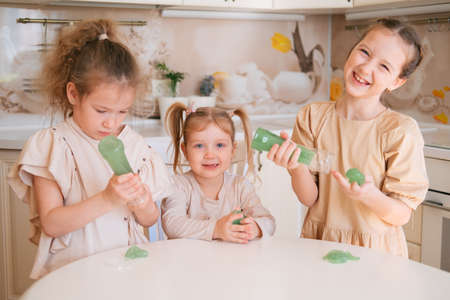 Three sisters playing slime on a kitchen, happy kids lifestyle. Banco de Imagens