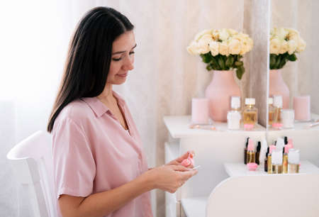 Cute caucasian woman with cotton disk and lotion in bedroom. Beauty self care concept.