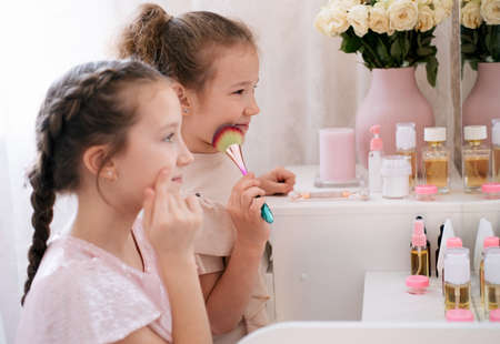 Two sisters making make up in a bedroom. Kids beauty care concept.