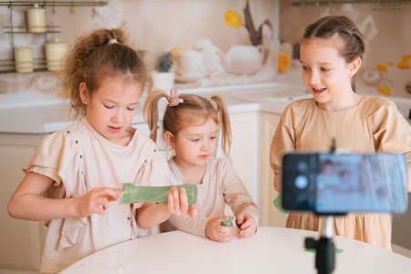 Three cute sisters playing slime on a kitchen and making video content for internet blog Banco de Imagens