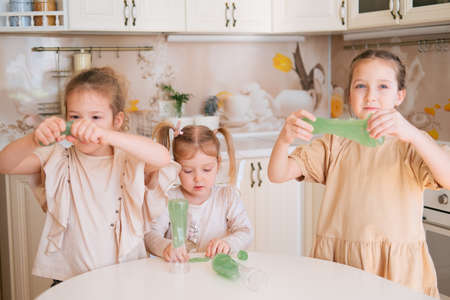 Three sisters playing slime on a kitchen, happy kids lifestyle. Foto de archivo