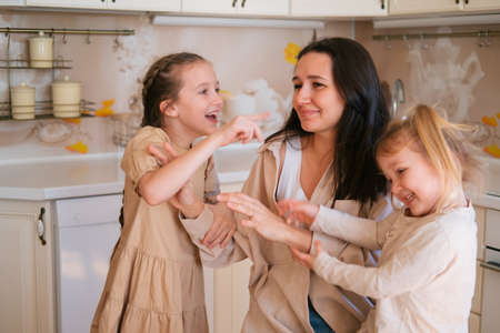 Mother playing with daughters in kitchen, positive lifestyle Foto de archivo