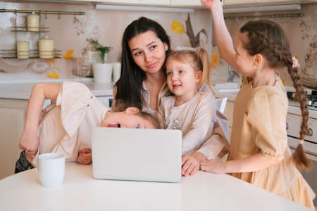 Young mother sitting with laptop on kitchen and three daughters interfere her work Banco de Imagens