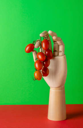 Modern minimal still life with wooden hand and tomatoes on green red background Stock Photo