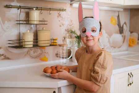 Cute little girl wearing rabbit mask holding plate with eggs. Easter preparation concept.