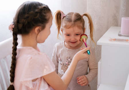The older sister does makeup for the younger sister. Cute family children's lifestyle. Banco de Imagens