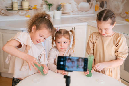 Three cute sisters playing slime on a kitchen and making video content for internet blog Foto de archivo