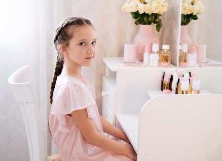 Elegant Caucasian girl sits on a chair near the dressing table and looking in the camera.