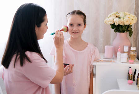 Mother runs a brush over her daughter's face. Makeup and parenting concept Foto de archivo