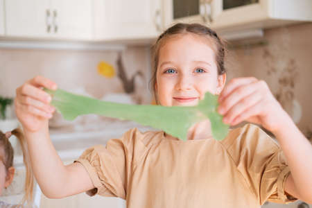 Cute young girl stretching green slime in kitchen, selective focus. Foto de archivo