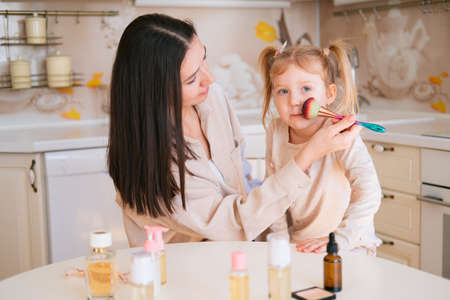 Young beautiful mother runs a brush over her little daughter's face. Makeup and parenting concept