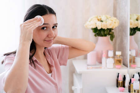 Cute caucasian woman touching face with cotton disk in bedroom. Beauty self care concept.