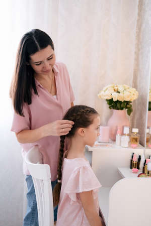 Young beautiful mother braids her daughter's pigtails.