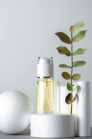 Luxury minimal still life with cosmetic product and eucalyptus leaves white products stands gray background Standard-Bild