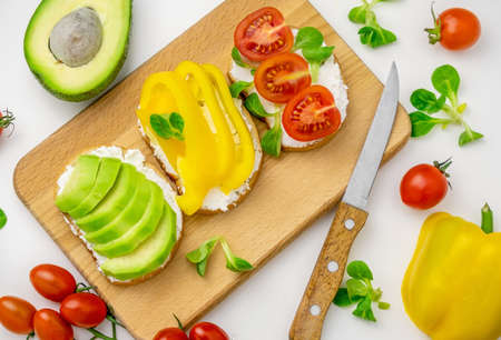 Homemade set of toasts with vegetables on wooden board on a white table