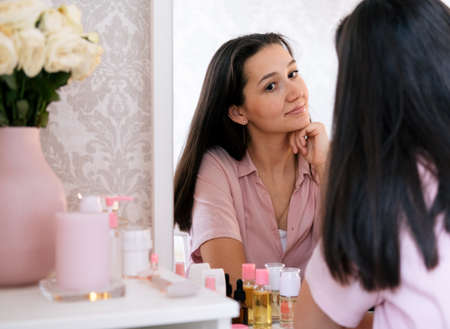 Beautiful brunette woman looking in the mirror. Beauty concept.