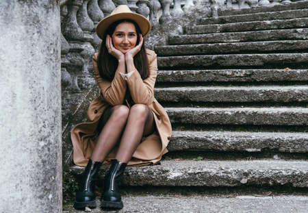 Beautiful young woman wearing beige hat and coat, sitting on stairs. Foto de archivo