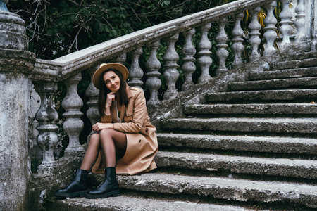 Beautiful young woman wearing hat and jacket, sitting on stairs. Travel concept. Banco de Imagens