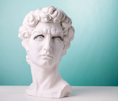Plaster statue head wearing eyelashes blue background