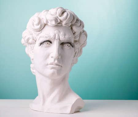 Plaster statue head wearing eyelashes blue background