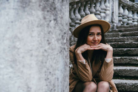 Portrait of beautiful young woman wearing beige hat and coat, sitting on stairs.