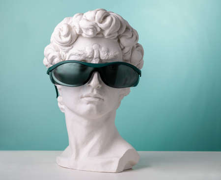 Plaster statue head blue background wearing sunglasses Banco de Imagens