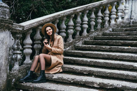 Beautiful young woman wearing hat and jacket, sitting on stairs. Travel concept. Foto de archivo