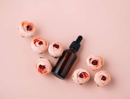 Top view flat lay cosmetic oil bottle and roses soft pink background. Beauty care concept