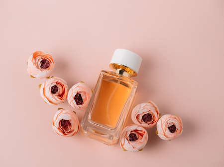 Top view flat lay golden perfume and roses, soft pink background, mock up, copy space. Foto de archivo