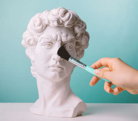 Plaster statue head blue background and female hand with make up brush
