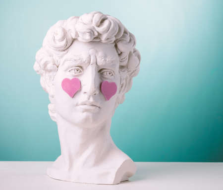 Plaster statue head with pink hearts blue background
