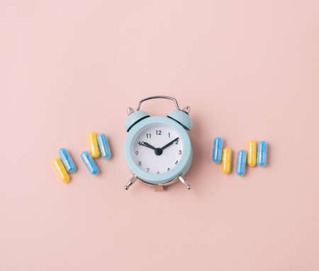 Top view flat lay medicine pills and alarm clock. Beige and blue. Medication time concept.