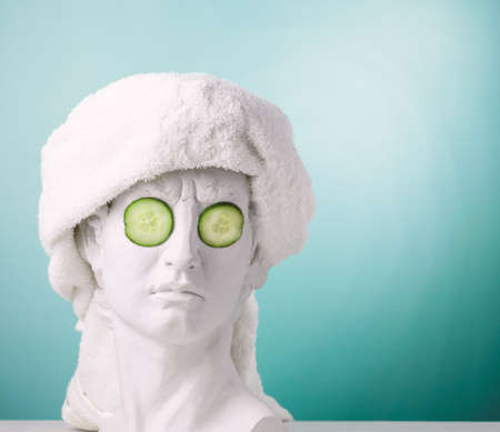 Plaster statue head blue background wearing white towel and cucumber face mask. Beauty care concept. Banco de Imagens