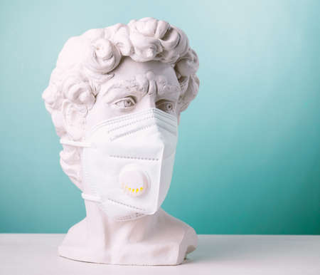 Plaster statue head blue background wearing medical mask Foto de archivo