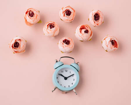 Top view flat lay alarm clock and roses soft pink background Foto de archivo