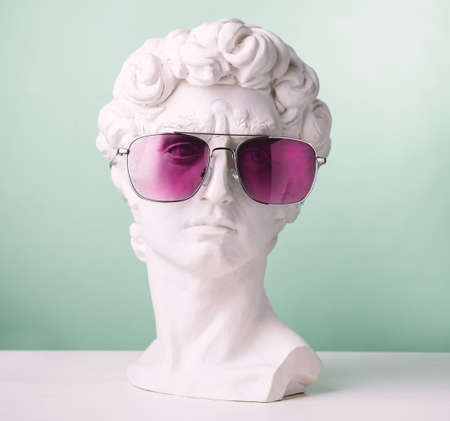 Plaster statue head green background wearing pink sunglasses Foto de archivo