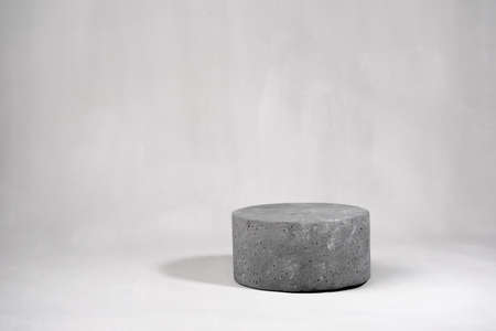 Empty round cylinder product stand on gray concrete background. Mock up. Copy space.