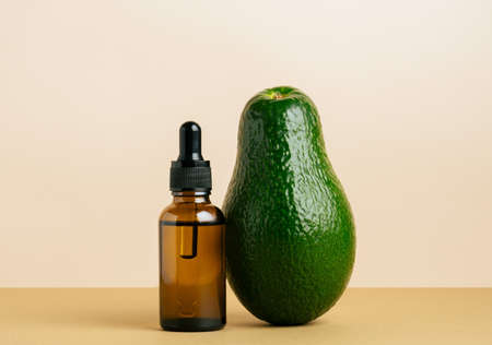 Essential avocado oil beige background. Beauty care concept. Banco de Imagens