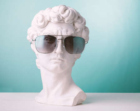 Plaster statue head blue background wearing sunglasses Foto de archivo