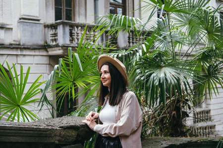 Beautiful caucasian woman in hat and casual beige clothes portrait on a background of palm leaves and ancient building Foto de archivo