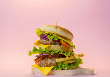 Big double meat burger on a pastel pink background. Fast food concept poster.
