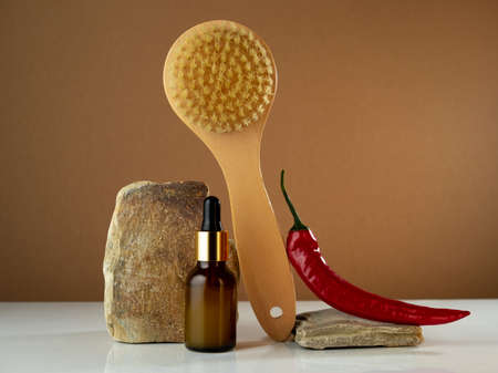 Cosmetic oil of burning red pepper and dry massage brush. Modern still life beauty care concept.